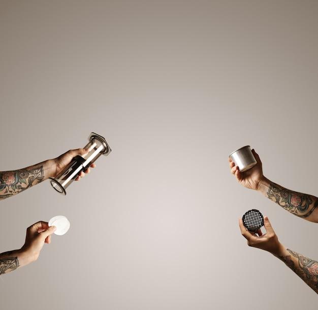 Vier handen met aeropress, filters, filterdop en stalen reisbeker reiken vanaf de zijkanten naar het midden op wit alternatieve commerciële koffie voor het zetten van koffie Gratis Foto