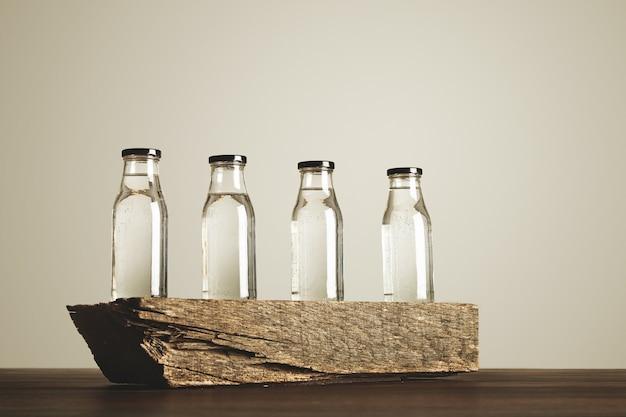 Vier helder transparante glazen flessen met zwarte doppen gevuld met zuiver drinkwater gepresenteerd op houten steen, geïsoleerd op wit Gratis Foto