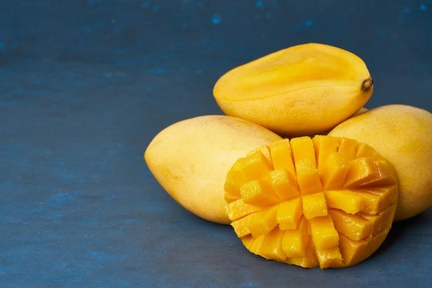 Vier hele mangovruchten op donkerblauwe tafel en in plakjes gesneden. grote sappige rijpe gele vruchten Premium Foto