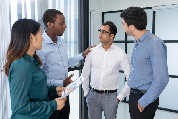 Vier jonge bedrijfsmensen die onderhandelingsstrategie bespreken alvorens partners te ontmoeten Gratis Foto