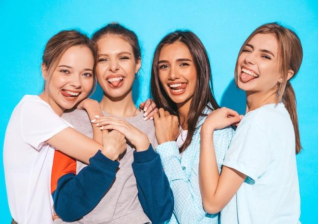 Vier jonge mooie glimlachende hipster meisjes in trendy zomerkleren. sexy onbezorgde vrouwen die dichtbij blauwe muur in studio stellen. positieve modellen die plezier hebben en knuffelen. ze tonen tongen Gratis Foto