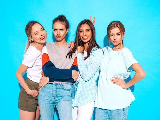 Vier jonge mooie glimlachende hipster meisjes in trendy zomerkleren. sexy onbezorgde vrouwen die dichtbij blauwe muur in studio stellen. positieve modellen die plezier hebben en knuffelen Gratis Foto