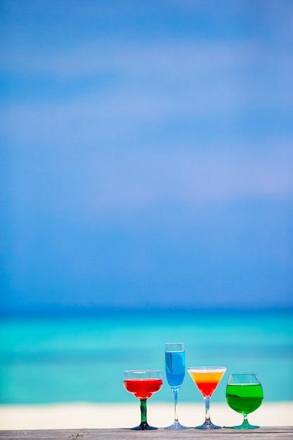 Vier kleurrijke exotische smakelijke cocktails turkooise overzees als achtergrond Premium Foto