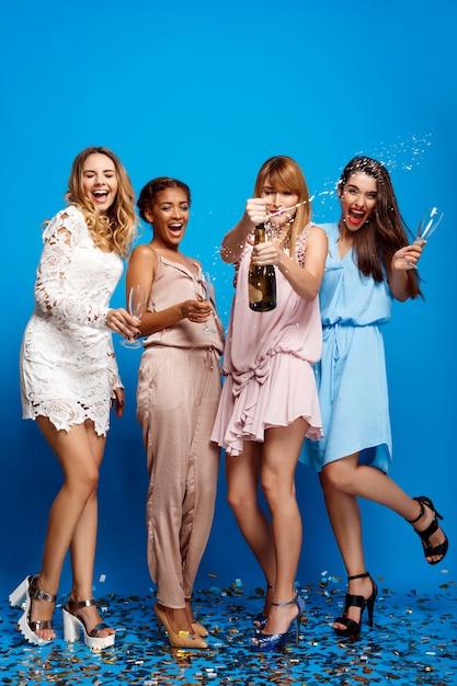 Vier mooie meisjes die bij partij over blauwe muur rusten Gratis Foto