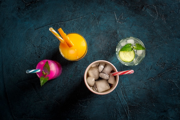 Vier soorten verfrissende drankjes met ijs op een donkerblauwe achtergrond en ijsblokjes. concept nachtclub, nachtleven, feest, dorst. sinaasappel, munt en komkommer, aardbei, cola. plat lag, bovenaanzicht Premium Foto