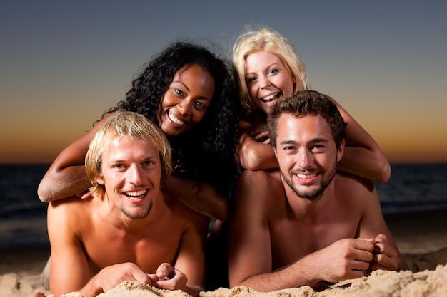 Vier vrienden op het strand met zonsondergang Premium Foto