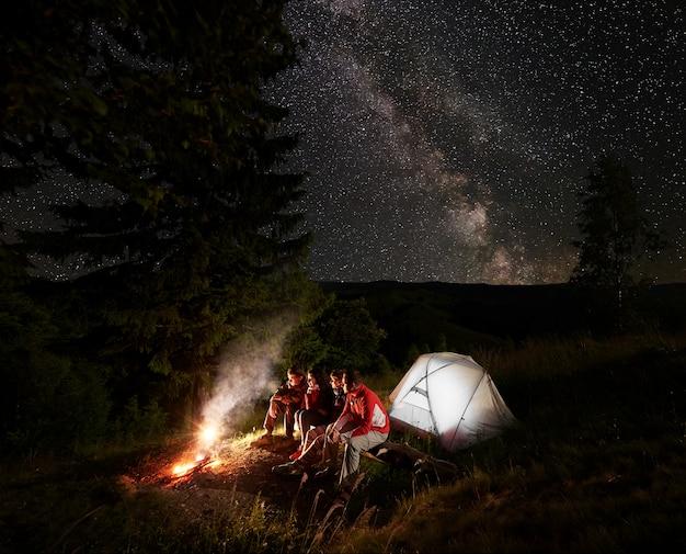 Vier vrienden zitten op een boomstam bij de tent en genieten van de vlam van een vuur bij de prachtige dennenbomen onder de sterrenhemel waarop de melkweg zichtbaar is tegen de achtergrond van bergen en heuvels. Premium Foto