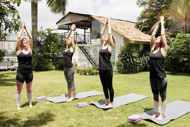 Vier vrouwen beoefenen van yoga buitenshuis doen de zonnegroet pose Gratis Foto