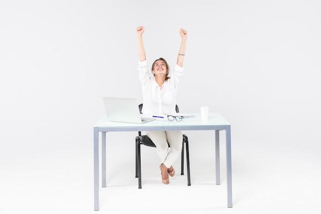 Vierende onderneemster bij bureau met laptop die op witte achtergrond wordt geïsoleerd Gratis Foto