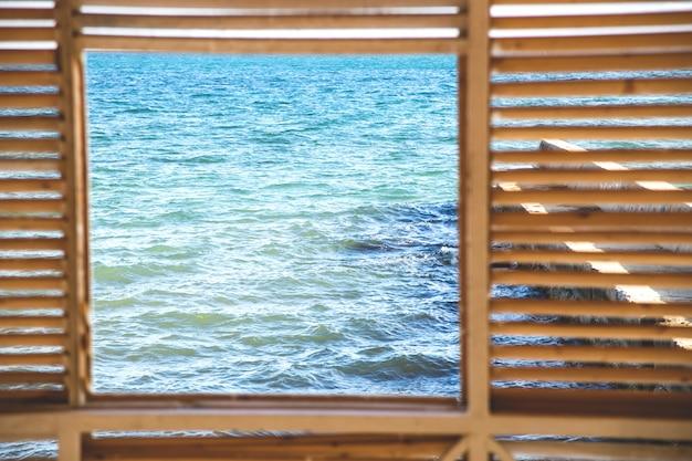 Vierkant raam met uitzicht op de blauwe zee en de blauwe lucht. Premium Foto