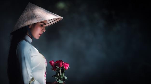 Vietnamees meisje in een witte jurk draagt een hoed en de rode rozen in hand in hand Premium Foto