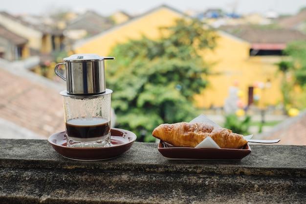 Vietnamese koffie en croissant op tafel Premium Foto
