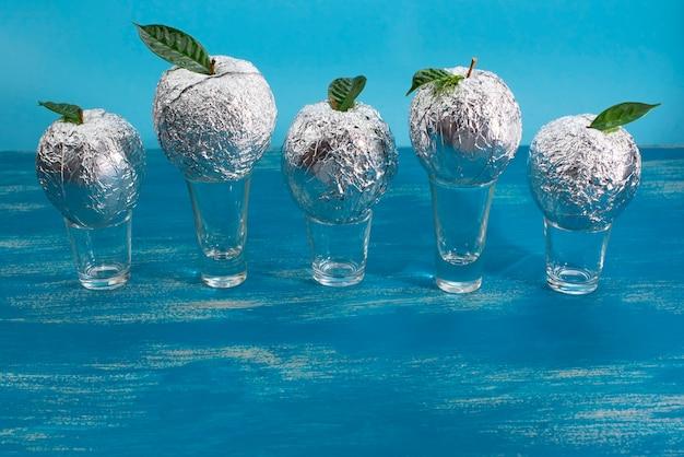 Vijf appels in de schaal folie met natuurlijke groene bladeren. Premium Foto