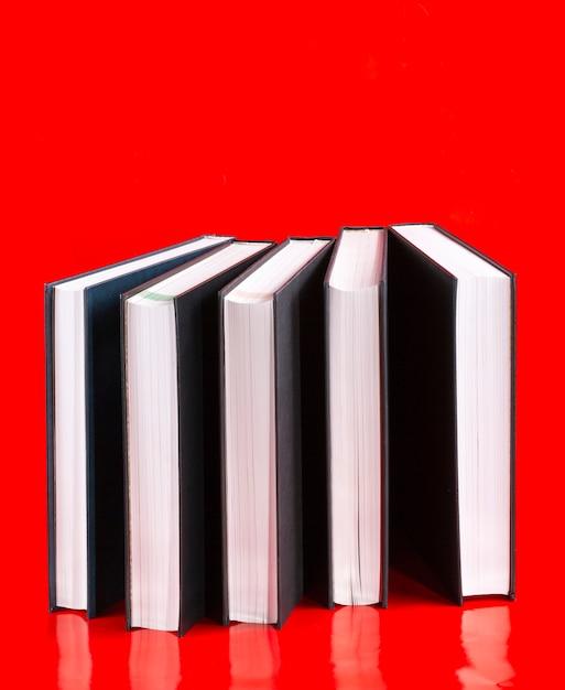 Vijf boeken op een rode achtergrond Premium Foto