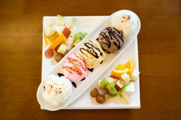Vijf bolletjes ijs geplaatst in een lang bord op tafel Premium Foto