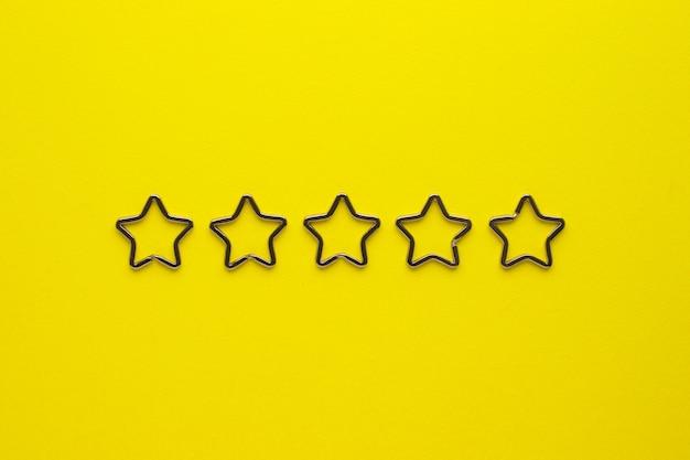 Vijf glanzende metalen split-sleutelhangers in de vorm van een ster voor sleutelhangers. verchroomde sleutelhangersluiting op gele achtergrond. Premium Foto