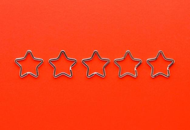 Vijf glanzende metalen split-sleutelhangers in de vorm van een ster voor sleutelhangers. verchroomde sleutelhangersluiting op rode achtergrond. feedback Premium Foto