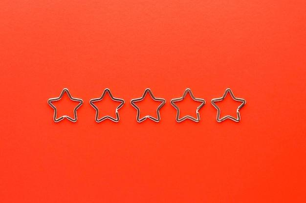 Vijf glanzende metalen split-sleutelhangers in de vorm van een ster voor sleutelhangers. verchroomde sleutelhangersluiting op rode achtergrond. Premium Foto