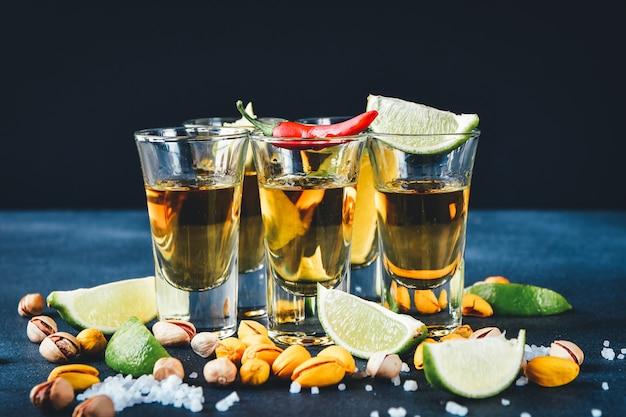 Vijf glazen alcohol met snacks limoen en pistache, zout en chilipeper voor decoratie. tequila-shots, wodka, whisky, rum Premium Foto