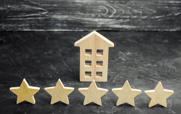 Vijf sterren en een houten huis op een grijze concrete achtergrond. Premium Foto