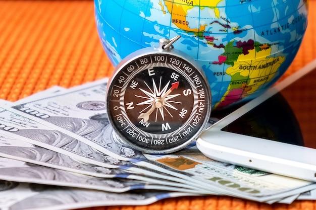 Vijfhonderd amerikaanse dollar bankbiljetten, kompas, bol van de planeet aarde Premium Foto