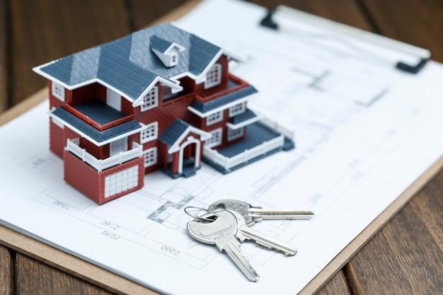 Villa huis model, sleutel en tekening op retro desktop (onroerend goed verkoop concept) Gratis Foto