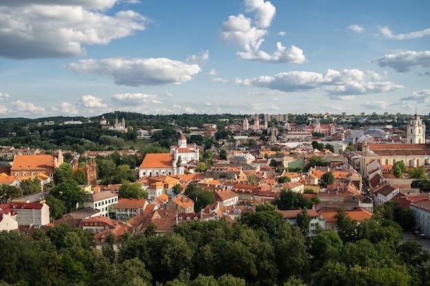 Vilnius stad omgeven door gebouwen en groen onder zonlicht en een bewolkte hemel in litouwen Gratis Foto