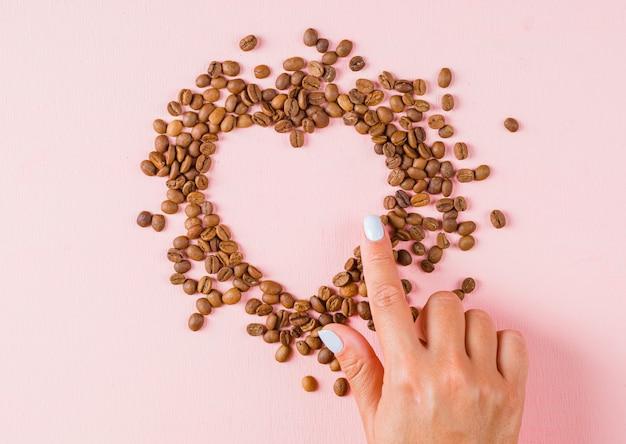 Vinger die hartopening van koffiebonen toont Gratis Foto