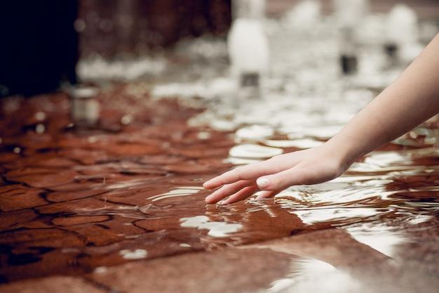 Vinger raakt water van dichtbij. zorg voor natuur, milieubescherming, gebrek aan drinkwater op de planeet. contact tussen mens en natuur. milieuactiviteit. hand raakt het water aan. Premium Foto