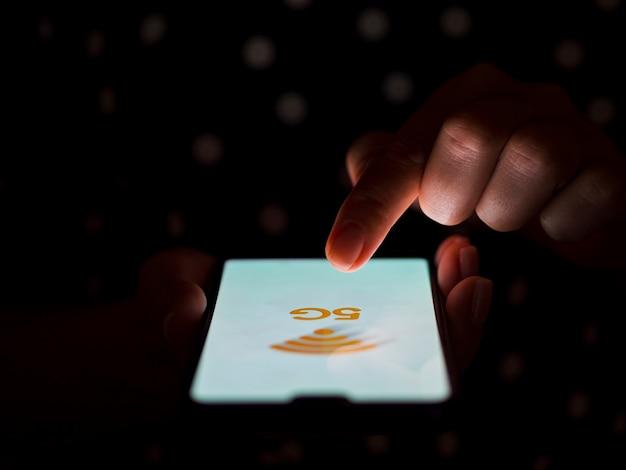 Vinger wat betreft de donkere achtergrond van het telefoonscherm Gratis Foto