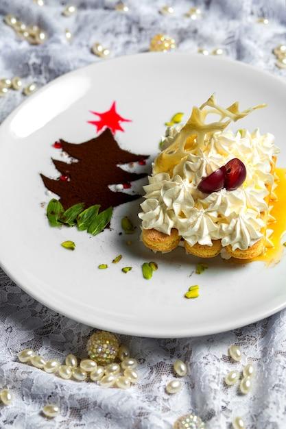 Vingerkoekjes die met room worden verfraaid die in saus dichtbij de kleine boom van het koffiepoeder wordt gediend Gratis Foto
