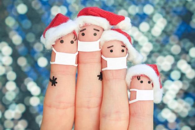 Vingers kunst van familie in medisch masker van covid-2019 viert kerstmis. Premium Foto