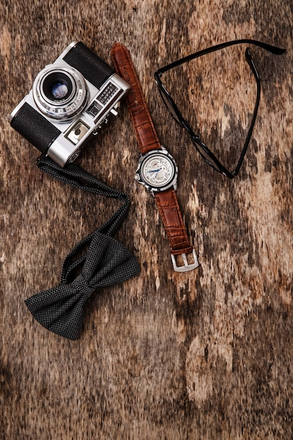 Vintage camera, polshorloge, bril en vlinderdas Gratis Foto