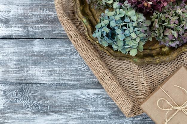 Vintage dienblad met gedroogde blauwe bloemen van hortensia's, geschenkdoos verpakt in kraftpapier op een jute op een grijze tafel. vlakke stijl Premium Foto