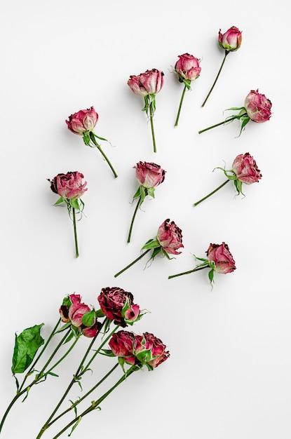Vintage florale achtergrond gemaakt van gedroogde rode rozen. plat liggen, boven het hoofd. Premium Foto