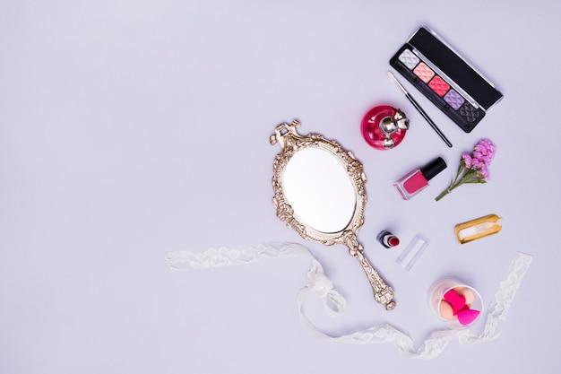 Vintage handspiegel; lippenstift; nagellak; spons; parfumflesje en oogschaduw palet op paarse achtergrond Gratis Foto