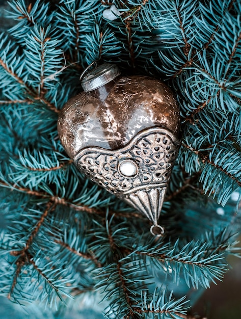 Vintage kerstboomdecoratie op een tak van een blauwe dennenboom Premium Foto