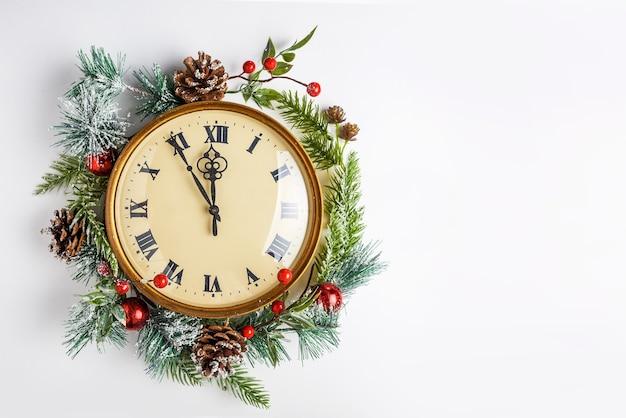 Vintage klok in een kerstdecor op een witte muur, twaalf uur, oudejaarsavond Premium Foto