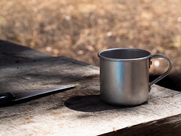 Vintage metalen mok en mes op armoedige houten tafel Gratis Foto