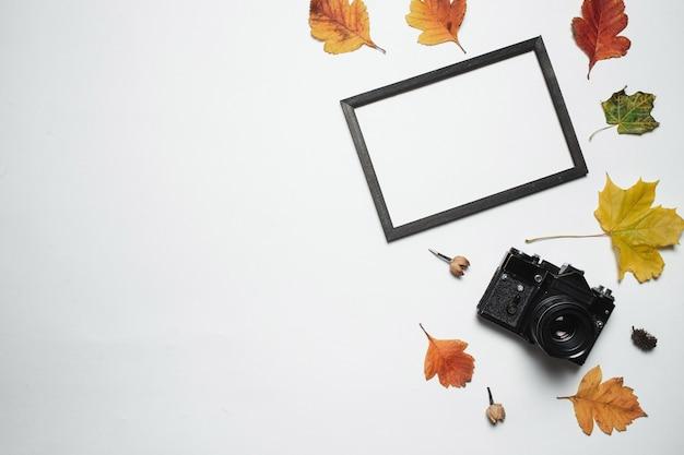 Vintage retro camera en houten fotolijst met herfstbladeren herfst. Premium Foto