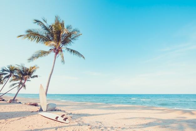 Vintage surfplank met palmboom op tropisch strand in de zomer. vintage kleurtoon Premium Foto