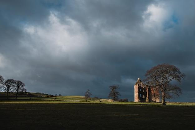 Vintage verwoeste kasteel 17e eeuw in het veld voor de stortbui, gilbertfield castle, glasgow, south lanarkshire, schotland Premium Foto