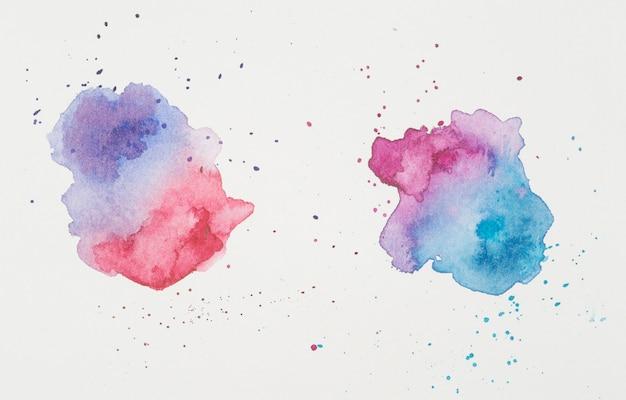 Violet en rood in de buurt van lila en aquamarijn vlekken van verven op wit papier Gratis Foto