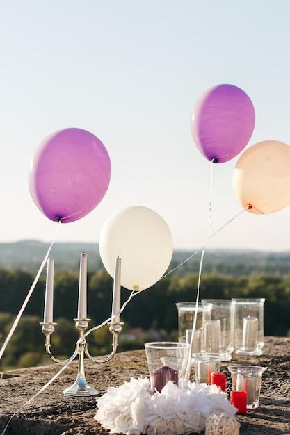 Violette en witte ballonnen zweven over de kaarsen Gratis Foto