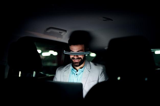 Virtuele realiteit concept. zakenman in de auto die laat werkt. Premium Foto