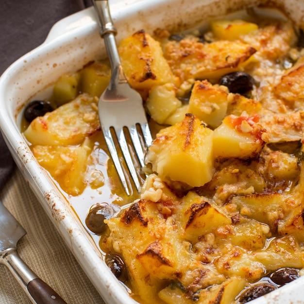 Vis met aardappelen en olijven gekookt in de oven in een kleine braadpan close-up Premium Foto