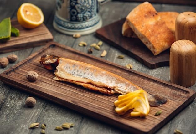 Vis op het houten bord met citroen Gratis Foto