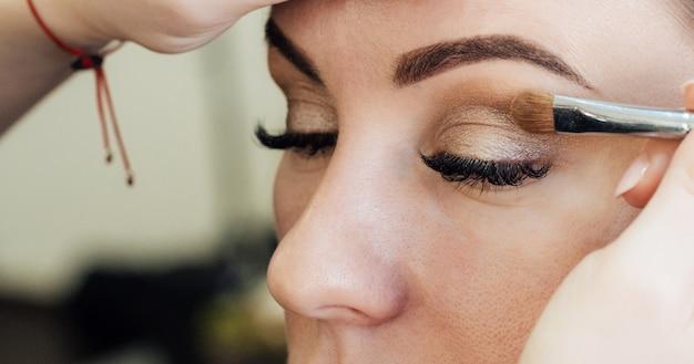 Visagist zet een penseelschaduw op de ogen van een vrouw in een schoonheidssalon Premium Foto