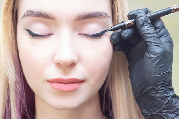 Visagist zet make-up op de ogen van het meisje. eyeliner. eyeliner eyeliner maken. schoonheidssalon Premium Foto