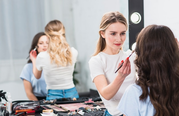 Visagiste die professionele make-upvrouw in studio creeert Gratis Foto